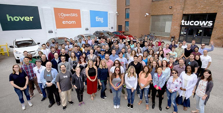 A photo of a large group of Tucows employees standing outside our offices in Toronto's Liberty Village.