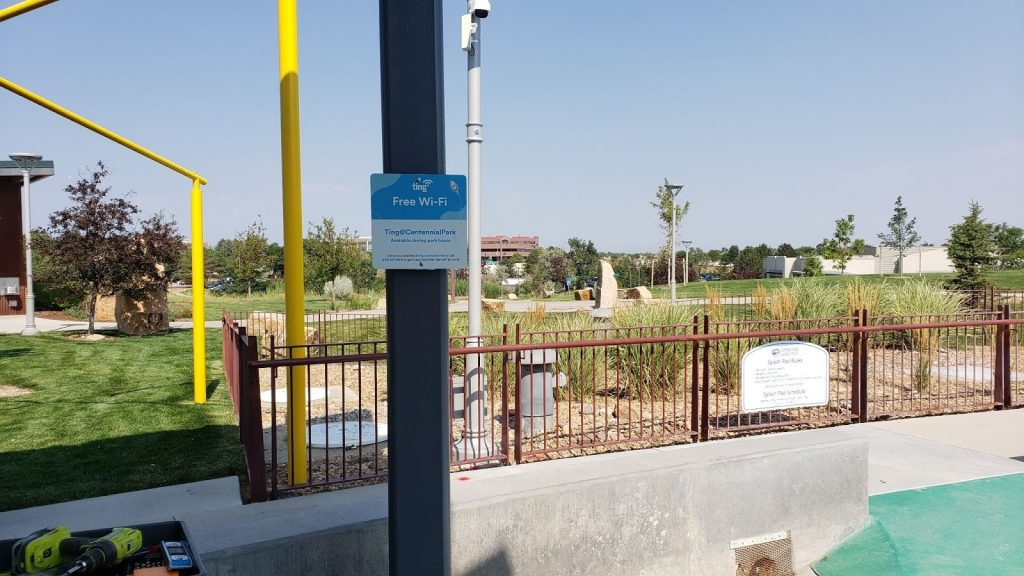 A sign that says Free Wi-Fi by Ting Internet attached to a poll at Centennial Park Colorado.